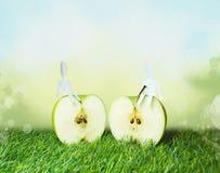 2 бумажных люд сидя на яблоке Стоковая Фотография