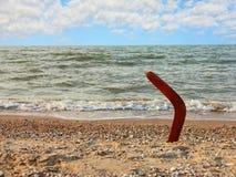 Бумеранг на песочной береговой линии против волны и неба моря Стоковая Фотография RF