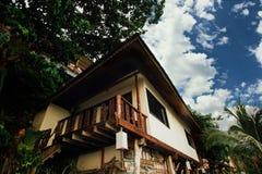 Бунгала среди тропических деревьев Дом лестницы на ходулях между тропическими ладонями стоковое фото
