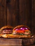 2 бургера закрывают вверх на разделочной доске Стоковая Фотография