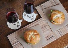 2 бургера на бумаге kraft на досках zebrano и 2 стеклах с красным вином на srtands в форме кота Взгляд сверху Стоковые Фотографии RF