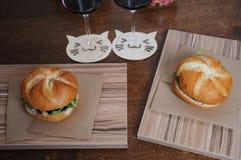 2 бургера на бумаге kraft на досках zebrano и 2 стеклах с красным вином на srtands в форме кота Стоковое Фото