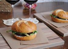 2 бургера на бумаге kraft на досках zebrano и 2 стеклах с красным вином на srtands в форме кота Стоковое Изображение