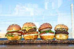 4 бургера на деревянной доске в ресторане Стоковые Изображения RF