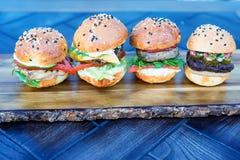 4 бургера на деревянной доске в ресторане Стоковые Фотографии RF
