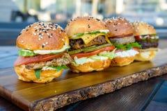 4 бургера на деревянной доске в ресторане Стоковое Изображение