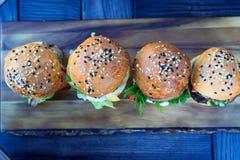 4 бургера на деревянной доске в ресторане Стоковая Фотография