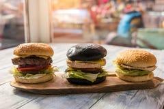 3 бургера на деревянной доске Стоковые Изображения