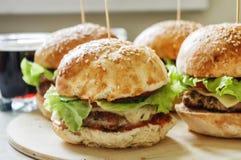 4 бургера на деревянной плите с колой Стоковые Изображения RF
