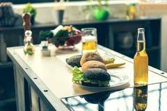 Бургеры аппетита и питье спирта на столе Стоковое Фото