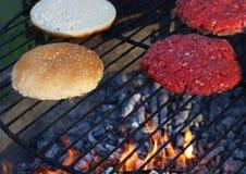 Бургеры и плюшки мяса для гамбургера на огне жарят Стоковая Фотография