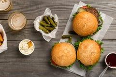 Бургеры и cheeseburger на деревянном столе с соусами и пивом Стоковое Изображение