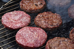 Бургеры мяса для гамбургера на гриле дыма Стоковое фото RF