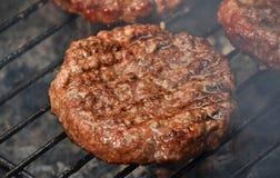 Бургеры мяса для гамбургера на гриле дыма Стоковые Фото