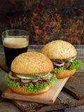 Бургеры Veggie с отбивной котлетой черных фасолей, салата, замаринованных луков, огурца и стекла темного пива на деревянной предп Стоковые Фото