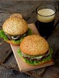 Бургеры Veggie с отбивной котлетой черных фасолей, салата, замаринованных луков, огурца и стекла темного пива на деревянной предп Стоковое Фото