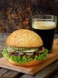 Бургеры Veggie с отбивной котлетой черных фасолей, салата, замаринованных луков, огурца и стекла темного пива на деревянной предп Стоковые Изображения RF