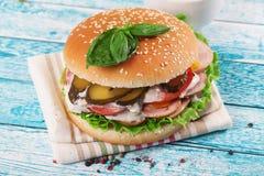 Бургер еды домашний на доске деревянного стола яркой с семенами сезама сосиски и плюшки Стоковые Изображения RF