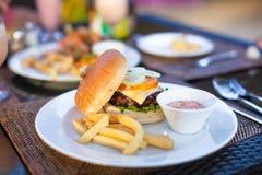 Бургер и фраи на белой плите для обеда стоковые фото