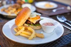 Бургер и фраи на белой плите для обеда стоковые изображения