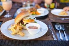 Бургер и фраи на белой плите для обеда стоковые изображения rf