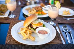 Бургер и фраи на белой плите для обеда стоковое фото