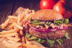 Бургер и французские фраи закрывают вверх на деревянной предпосылке Стоковая Фотография RF
