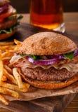 Бургер и французские фраи закрывают вверх на деревянной предпосылке Стоковые Изображения RF