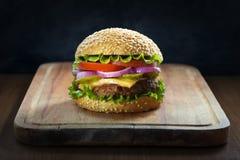 Бургер на деревянной разделочной доске, на темной предпосылке Стоковое Фото