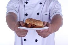 Бургер на плите в руках шеф-повара Стоковое Изображение