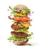 Бургер с ингридиентами летания стоковые изображения rf