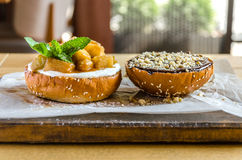 Бургер с семенами сезама, с шоколадом, гайками, ананасом и мятой, на деревянной доске Взгляд со стороны Стоковая Фотография
