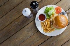 Бургер, французские фраи, соус в плите на деревянном столе Стоковое Изображение RF