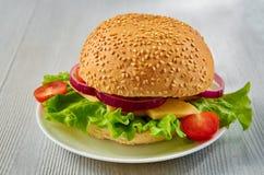 Бургер Veggie с салатом, кольцами лука, сыром и томатами вишни на серой конкретной таблице Классический американский вегетарианск Стоковые Фотографии RF