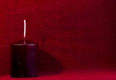 Бургундская свеча на красной бумаге предпосылки, торжество воска Стоковые Изображения RF