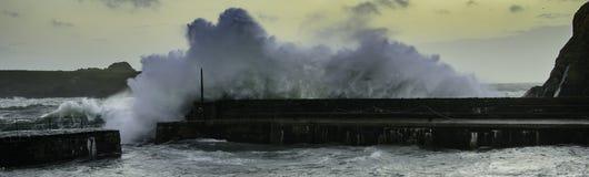 Stormy ocean waves crash over harbour wall Стоковые Фотографии RF