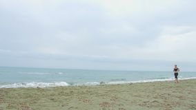 Бурное взморье, серые облака на горизонте Ход молодого брюнет женский на пляже сток-видео