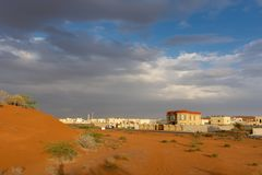 Бурный вечер в ОАЭ с темными облаками и голубым небом над городом и оранжевыми песчанными дюнами стоковая фотография