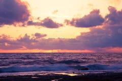 Бурный заход солнца на среднеземноморском Облака и волны тонизировано Стоковая Фотография