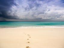 Бурный пляж с следами ноги на песке Стоковые Изображения