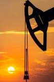 Буровая вышка над оранжевым небом Стоковая Фотография