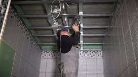 Буровая скважина работника для того чтобы зафиксировать профили потолка Пыль падая на человека разнорабочего акции видеоматериалы