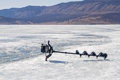 Буровая установка на льде Lake Baikal на предпосылке горы Стоковые Фото