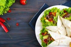 Буррито с прерванным мясом, авокадоом, овощами, горячим перцем на плите на темной деревянной предпосылке Стоковая Фотография