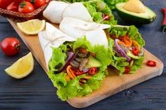 Буррито с прерванным мясом, авокадоом, овощами, горячим перцем на плите на темной деревянной предпосылке Стоковое Изображение