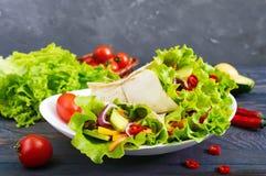 Буррито с прерванным мясом, авокадоом, овощами, горячим перцем на плите на темной деревянной предпосылке Стоковые Фотографии RF