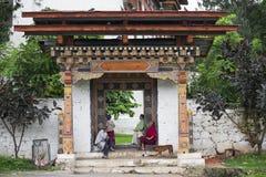 Бутанец сидит и имеет остатки в воротах монастыря, Бутана стоковая фотография rf