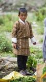 Бутанский мальчик носит традиционное пальто, стойку около chili, Бутана стоковая фотография rf