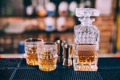Бутылка вискиа, кристаллические стекла и инструменты коктеиля в современном баре, на счетчике Стоковая Фотография