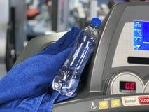 Бутылка воды и полотенце на приборе тренировки стоковое фото